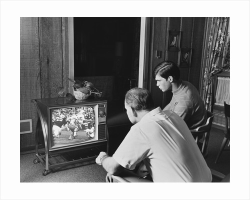 Teen boy watching football game on television with adult dad by Corbis