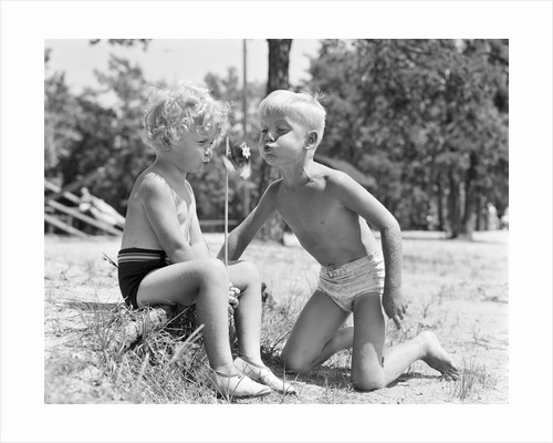 Blonde boy girl wearing bathing suits blowing on a pinwheel toy summer by Corbis