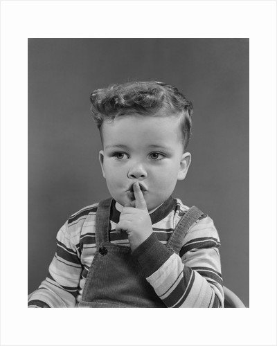 Little boy making shush shushing quiet silence sign with finger to mouth lips by Corbis
