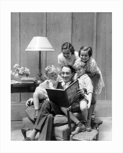 Father reading to family in chair by Corbis