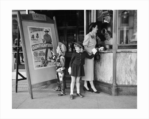 Mother and 2 children buying tickets to movie matinee boy wearing cowboy costume by Corbis
