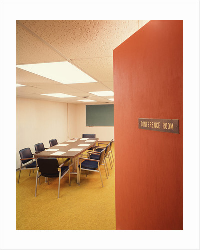 Conference room interior with table chairs chalkboard open door ajar by Corbis