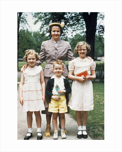 Mother and three children all dressed up posing for photo outdoors by Corbis