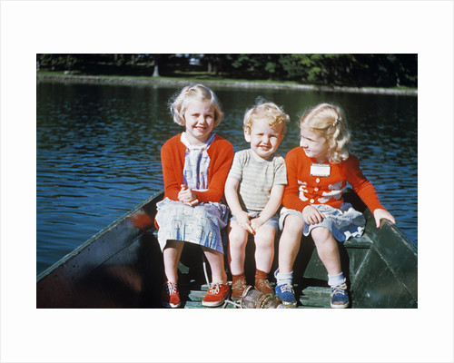 Boy and two girls in red sweaters sitting in back of rowboat by Corbis