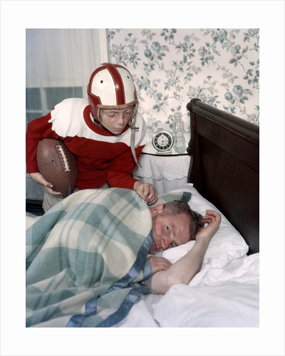 Boy in football uniform waking father asleep in bedroom by Corbis