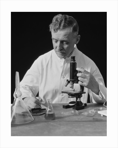 Male scientist wearing white lab coat writing data on clip board holding focus control of microscope by Corbis