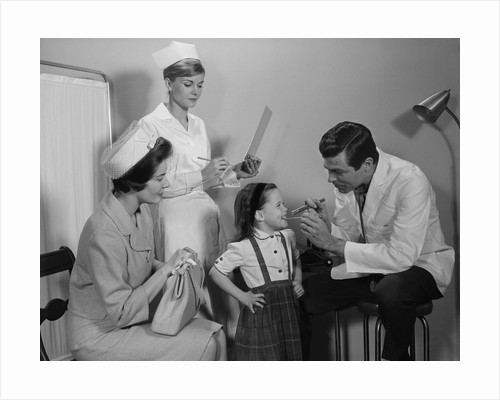 Mother sitting watching man pediatric doctor woman nurse checking on smiling little girl patient by Corbis