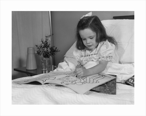 Little girl patient in hospital bed writing in coloring book by Corbis