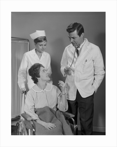 Man doctor woman nurse talking to smiling female patient sitting in hospital wheelchair by Corbis