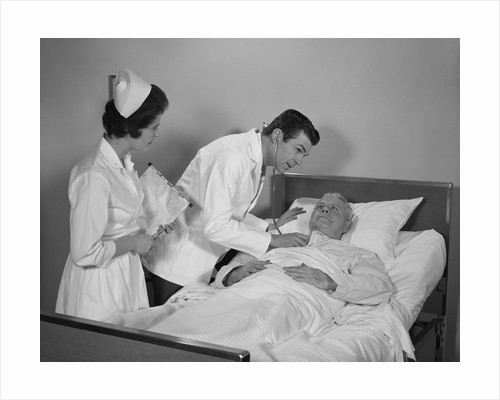 Doctor and nurse checking on elderly male patient in hospital bed by Corbis