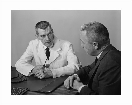 Doctor sitting at desk talking to male patient by Corbis