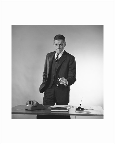 Serious businessman three piece suit standing behind desk gesturing with glasses by Corbis