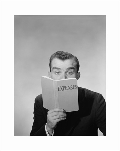 Man wide open eyes looking into expenses book hiding his lower face by Corbis