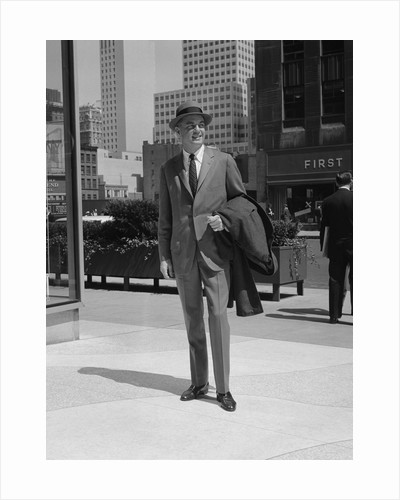 Businessman wearing suit hat carrying top coat standing on city street by Corbis