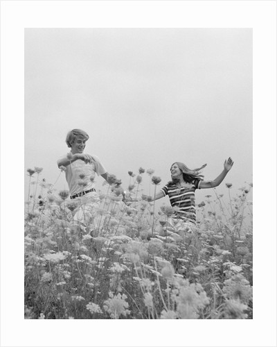 Young couple holding hands running through field of flowers by Corbis