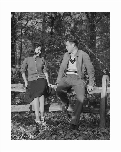 Young couple sitting on fence autumn smiling at one another by Corbis
