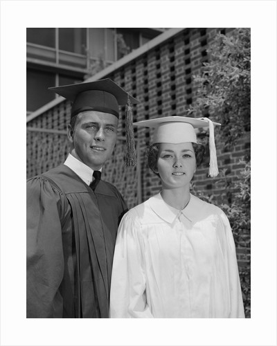 Graduation couple in cap and gown by Corbis