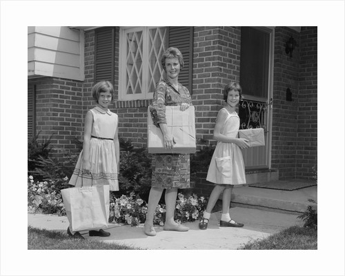 Mother and two daughters carrying shopping bags packages into house by Corbis