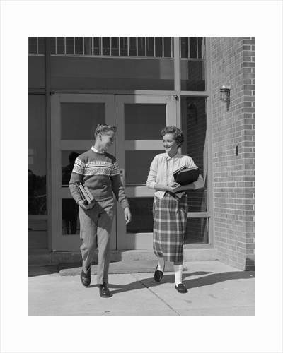Two teenage students boy and girl walking away from school doors carrying books by Corbis
