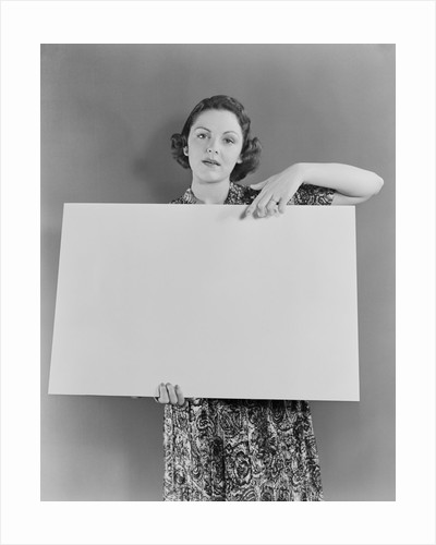 Woman holding blank poster sign hand pointing from top by Corbis