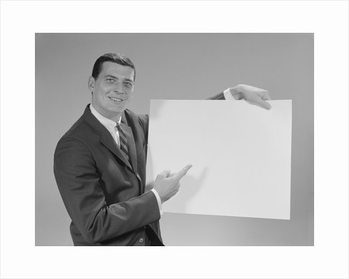 Smiling man pointing to blank poster by Corbis