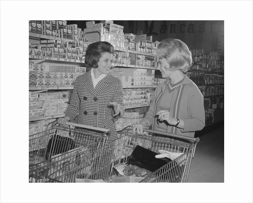 Two women talking shopping supermarket by Corbis