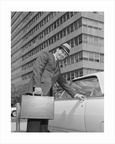 Businessman carrying briefcase getting into car on urban street by Corbis