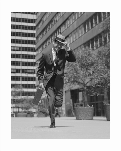 Businessman carrying briefcase holding his hat on running down urban sidewalk by Corbis