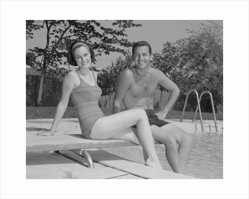Man woman couple sitting on diving board on side of swimming pool by Corbis
