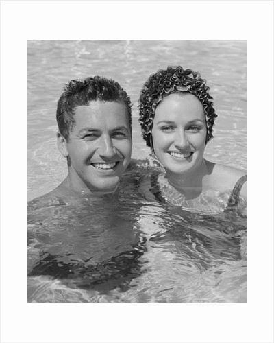 Smiling couple man woman in swimming pool by Corbis