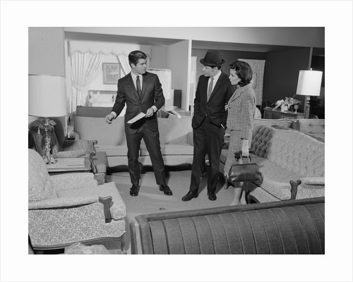 Furniture store salesman talking to couple by Corbis