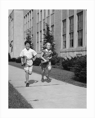 Boy girl running down sidewalk carrying school books smiling by Corbis
