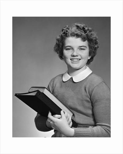 Adolescent teen girl smiling portrait holding school books by Corbis