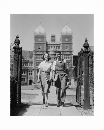 College aged student couple walking through campus gates university of pennsylvania by Corbis