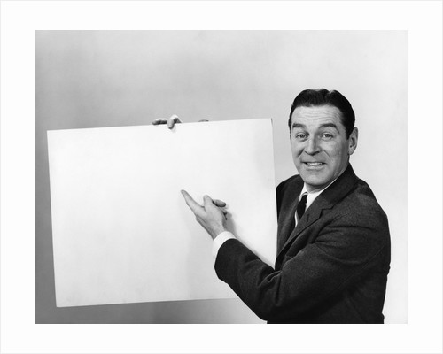 Smiling man pointing to blank poster sign by Corbis