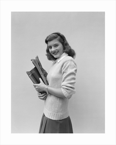 Smiling brunette teen student wearing sweater carrying school books by Corbis