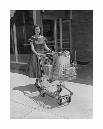 Smiling woman pushing grocery cart out of supermarket by Corbis