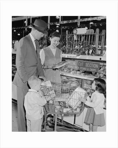 Family of 4 inside supermarket father pushing cart mother 2 kids by Corbis