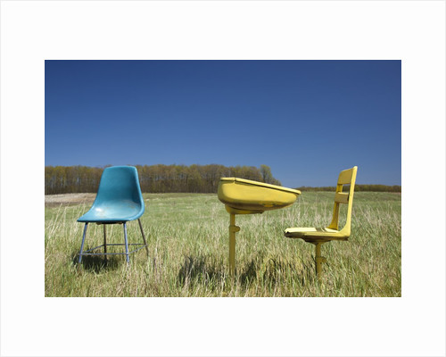 Abandoned school desk anc chairs in field by Corbis