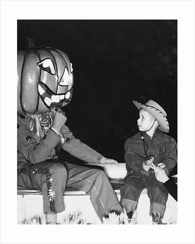 Young boy warily eyes pumpkin man, ca. 1955 by Corbis
