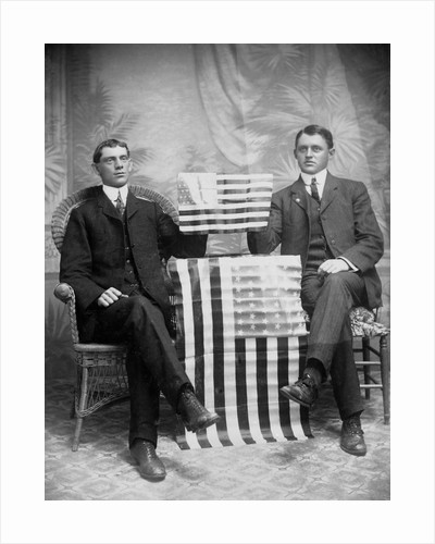 Two men pose with American flags, ca. 1895. by Corbis