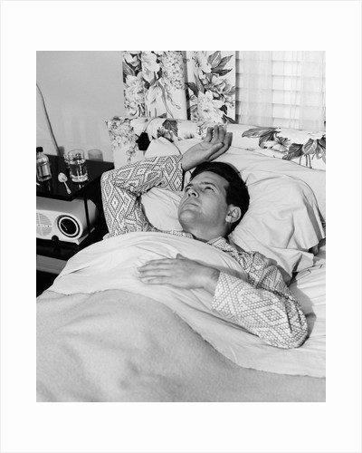 1940s 1950s sick man in bed in pajamas one hand on chest one above his head on pillow by Corbis