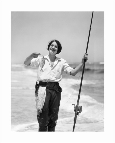 1920s 1930s smiling woman standing in ocean surf wearing rubber waders holding fish and fly fishing rod by Corbis