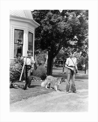 1940s boy with fishing gear collie dog second boy mowing grass with push mower by Corbis