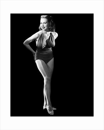 1950s busty young woman posing standing inside wearing bathing suit looking at camera by Corbis