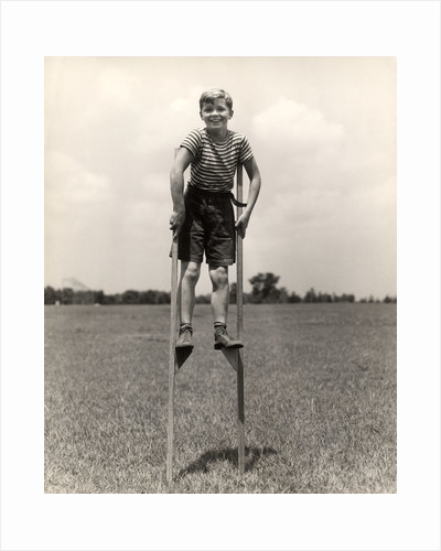 1930s 1940s smiling happy boy wearing striped shirt & short pants walking on pair of stilts looking at camera by Corbis