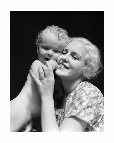 1930s blonde woman mother smiling holding baby to cheek by Corbis
