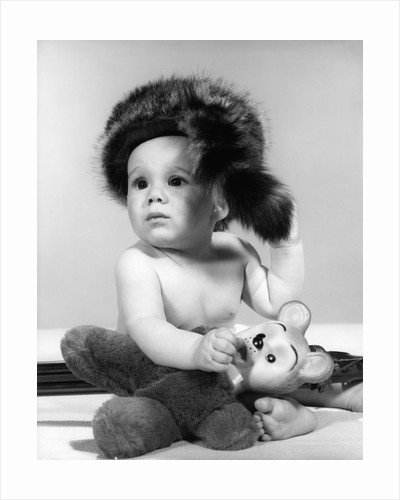 1960s baby wearing coonskin hat by Corbis