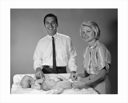 1960s smiling mother and father with twin babies on diaper changing table looking at camera by Corbis