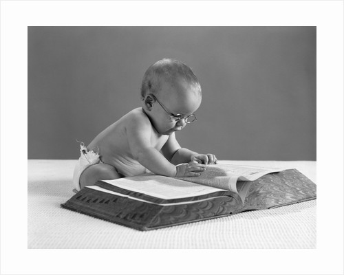 1960s baby wearing glasses looking for a word in big dictionary by Corbis